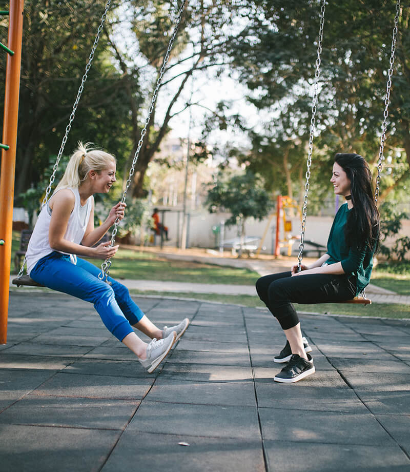 Two Women Swing In A Park